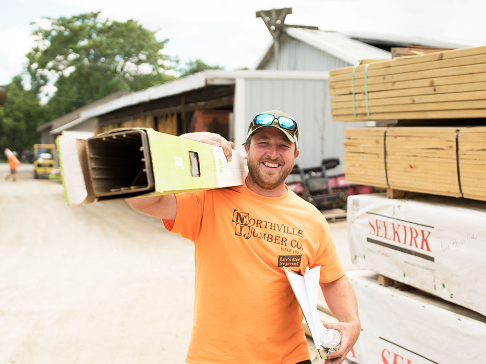 Smiling Northville Lumber worker carrying a deck post
