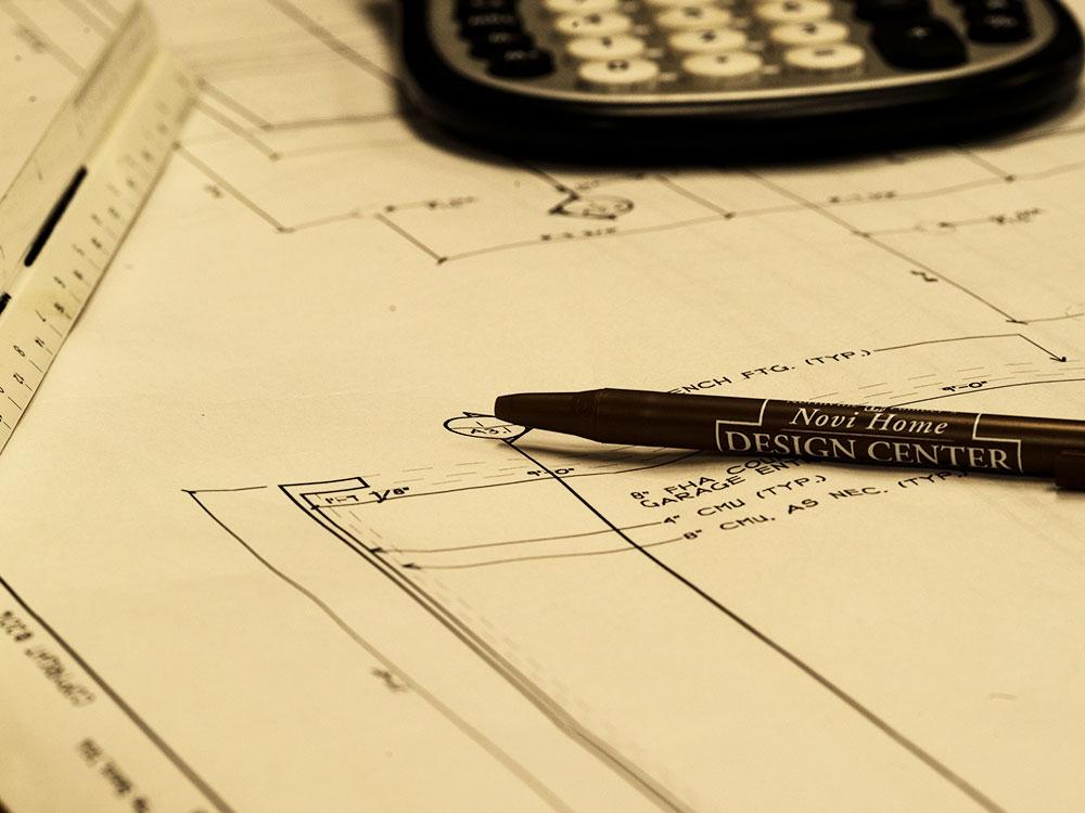 Construction blueprints, calculator, pen and scale ruler