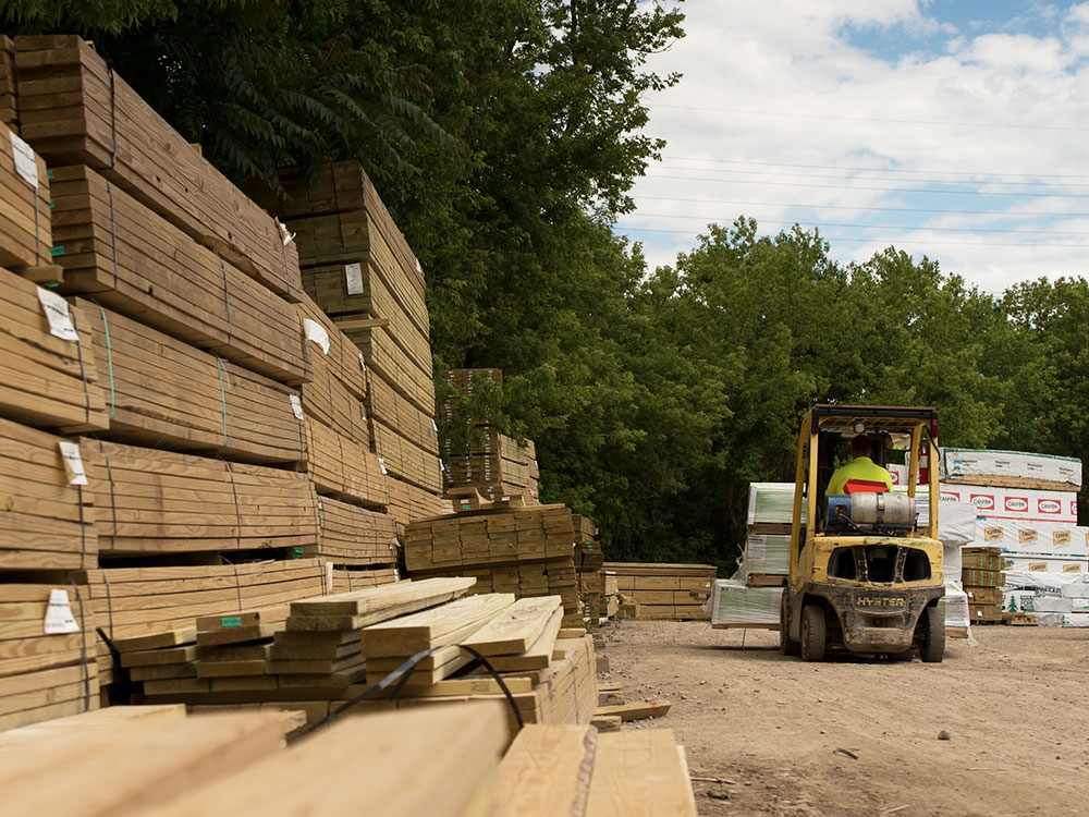 Stacks of lumber at our Northville Lumber yard with hi-lo in background